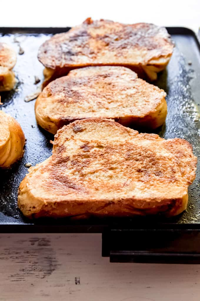 An image of golden brown french bread on an electric griddle.