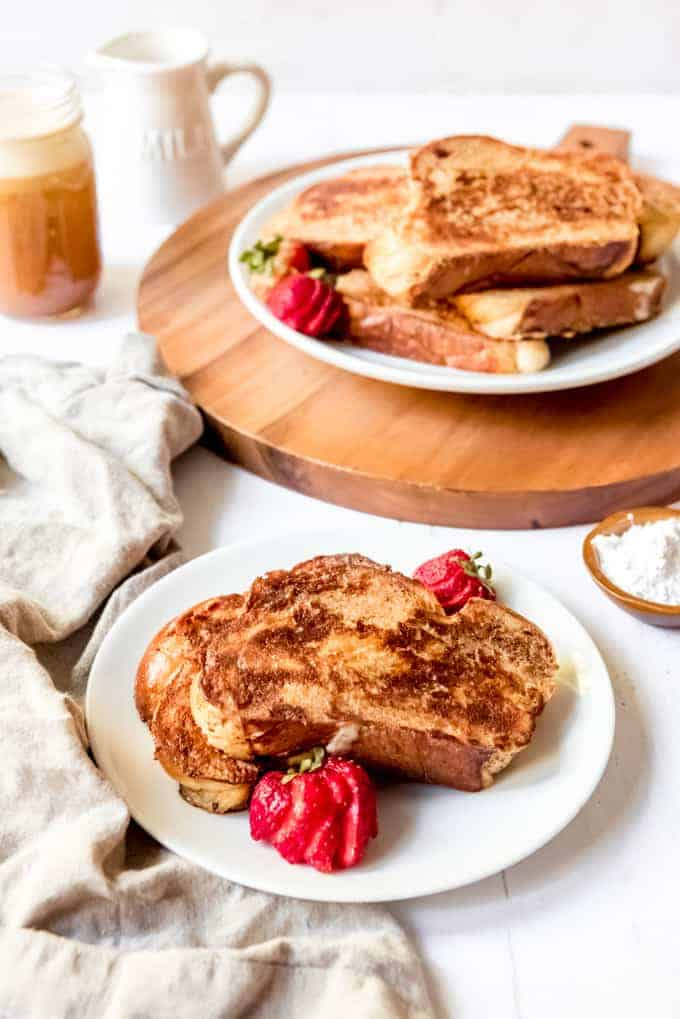 An image of two slices of french toast made with challah bread on a plate with a larger plate of french toast behind it.