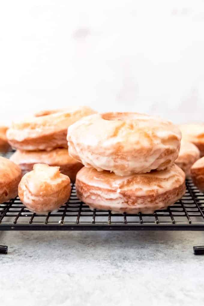An image of glazed old-fashioned donuts stacked on top of each other.