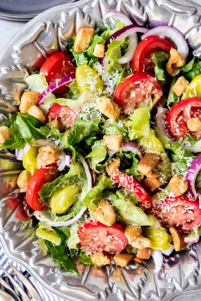 An image of a large silver serving bowl filled with salad ingredients.