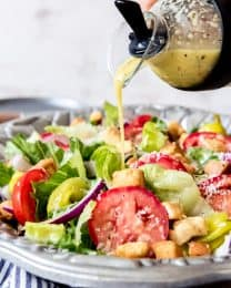 An image of homemade Olive Garden salad dressing being poured over a big bowl of salad with lettuce, tomatoes, red onions, croutons, and pepperoncini peppers.