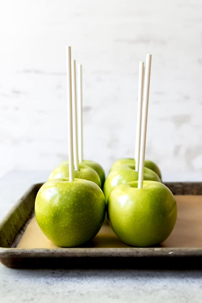An image of Granny Smith apples with sticks stuck in them.