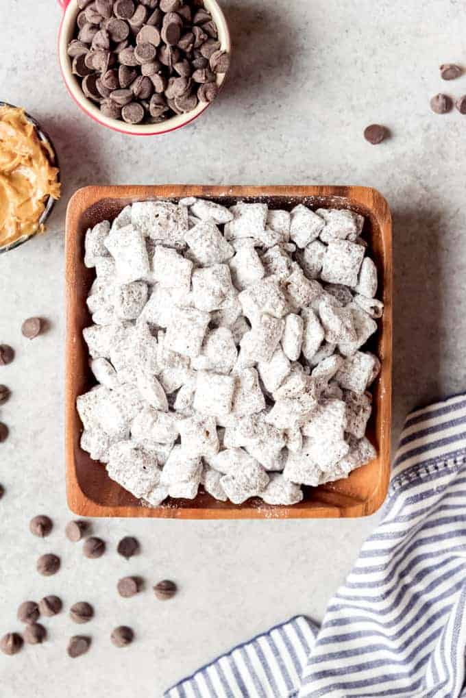 An image of a square wooden bowl filled with the best puppy chow dessert.