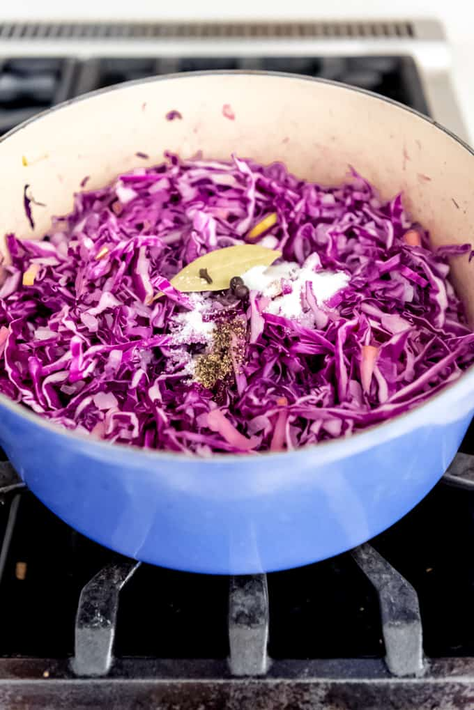 An image of red cabbage with spices in a dutch oven on the stovetop.
