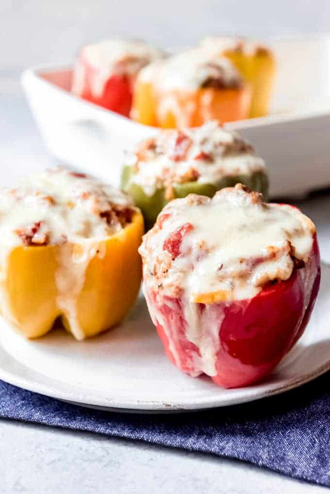 An image of red, yellow, and green stuffed peppers on a plate.