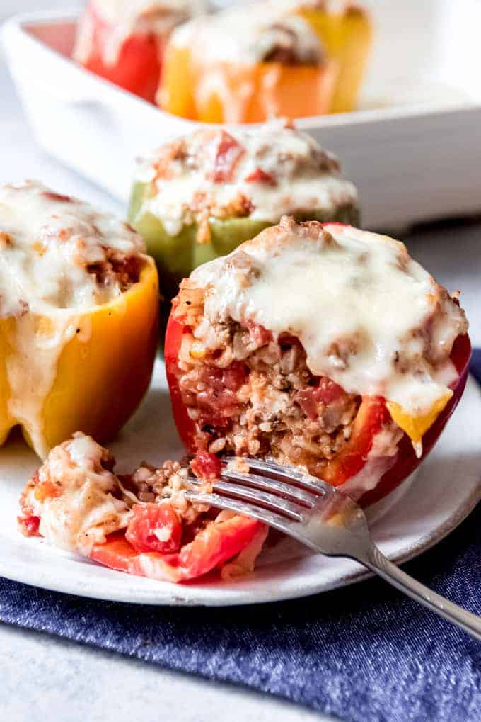 An image of a red stuffed bell pepper that is cut in half to show the insides of rice and ground beef, with melted cheese on top.