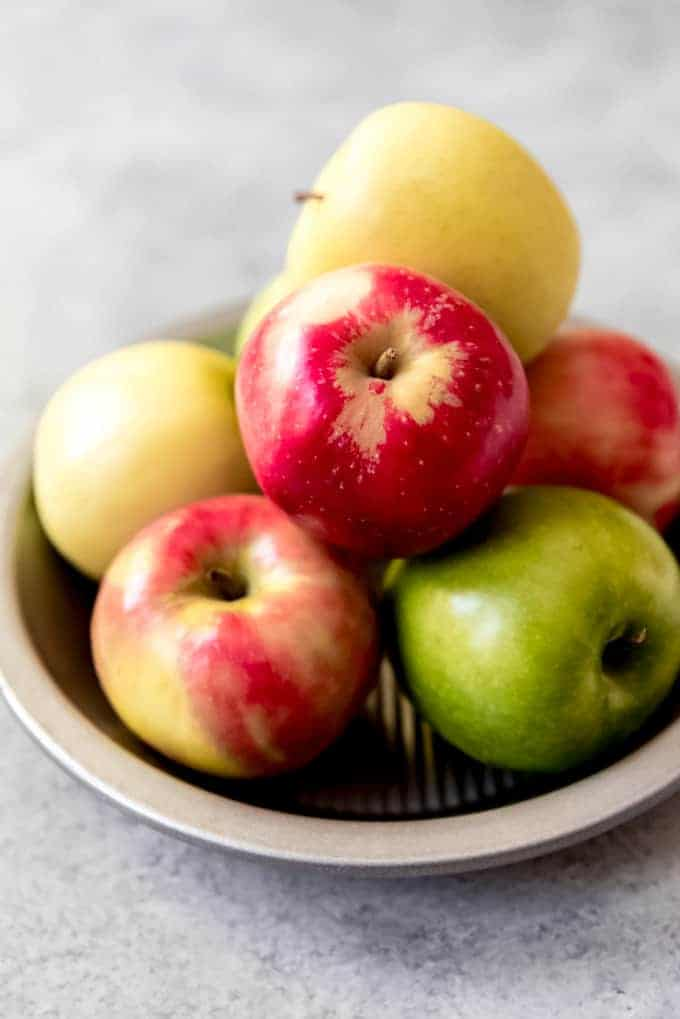 An image of Granny Smith, Pink Lady, and Golden Delicious apples in a pie plate.