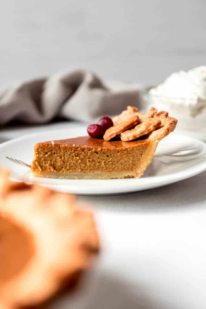 An image of a slice of classic pumpkin pie on a plate.