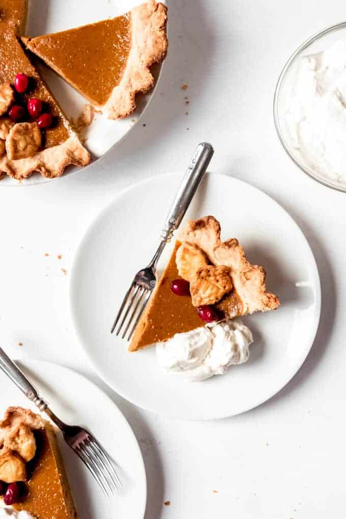 An image of a slice of homemade pumpkin pie on a plate with whipped cream on the side.