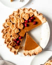 An image of a pumpkin pie with a slice taken out of it.