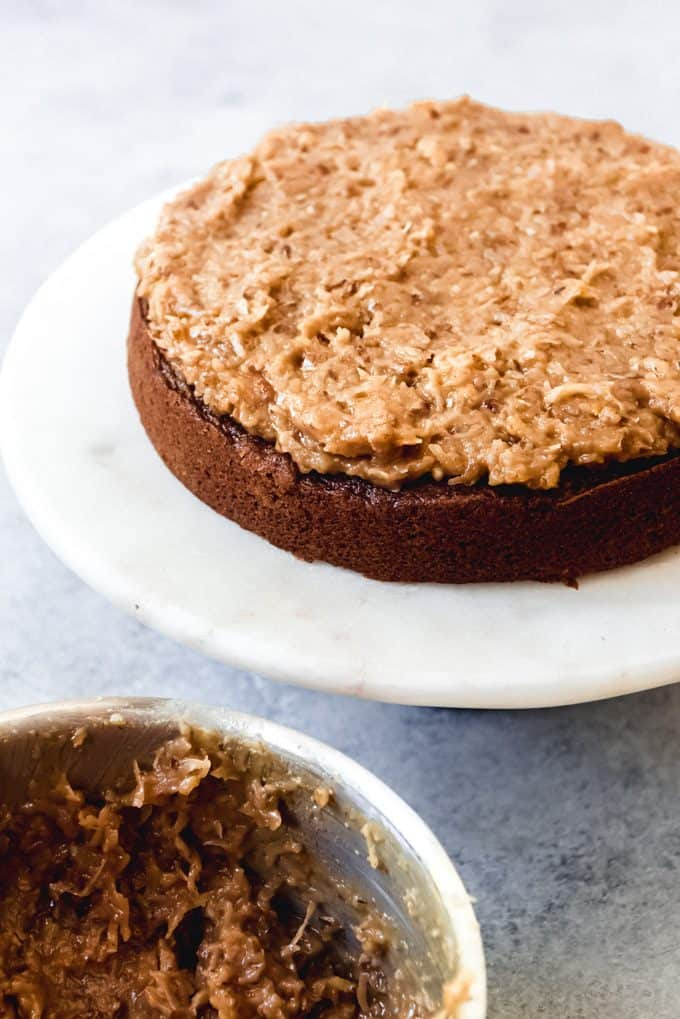 A layer of chocolate cake with coconut pecan frosting spread on top.