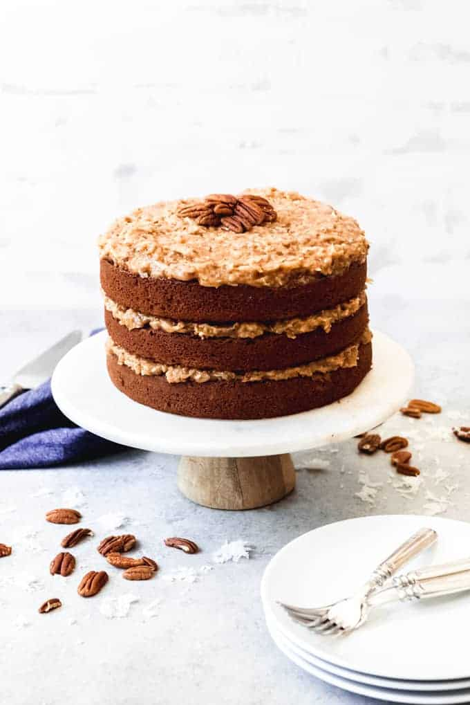 An image of a German chocolate cake on a white marble cake stand.