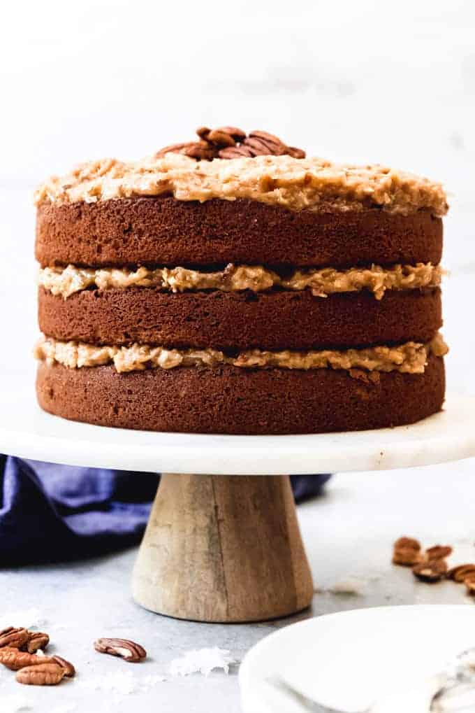 An image of a naked German Chocolate Layer Cake on a cake stand with coconut pecan frosting.