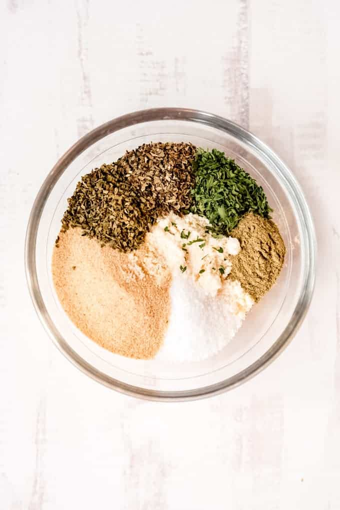 An image of Parmesan cheese, garlic powder, basil, oregano, parsley, marjoram, and salt for making garlic bread sprinkle.