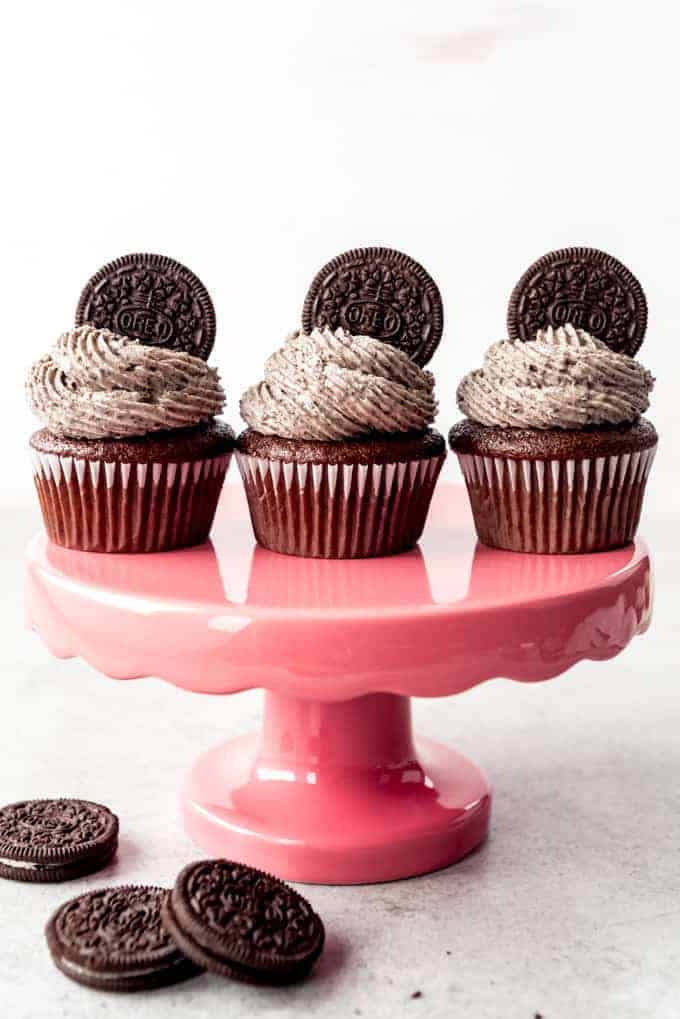 An image of three chocolate cupcakes with swirls of cookies and cream frosting on top.