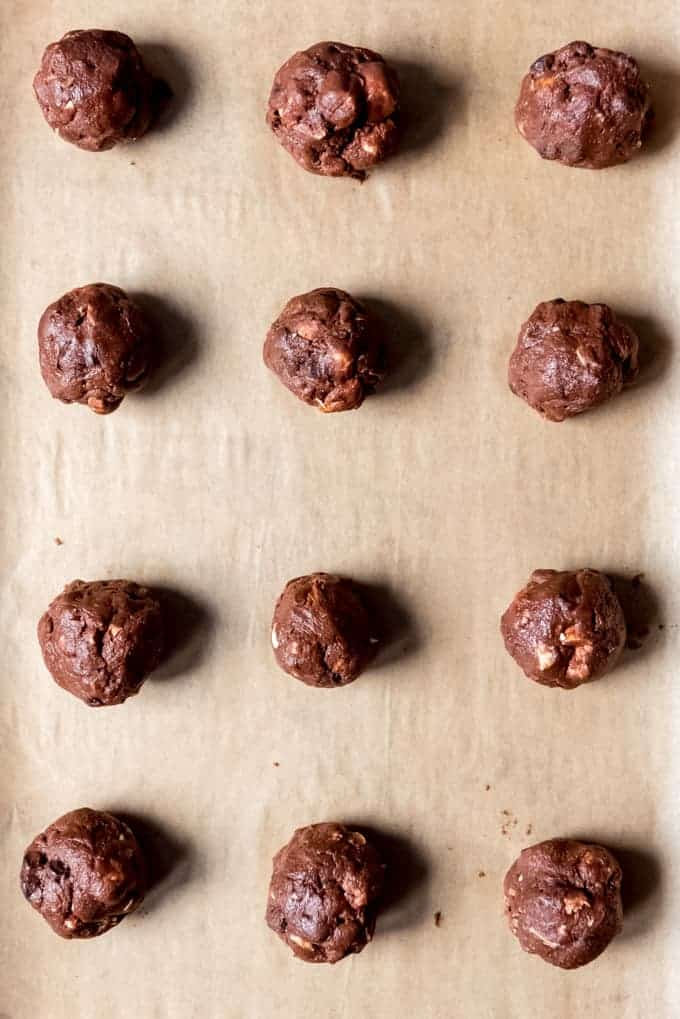 An image of balls or rocky road cookie dough on a baking sheet lined with parchment paper.