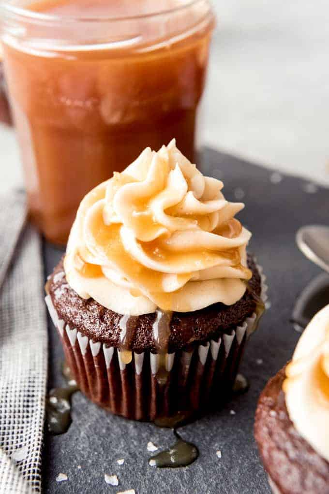 An image of a cupcake in front of a jar of caramel sauce with caramel dripping off the frosting.