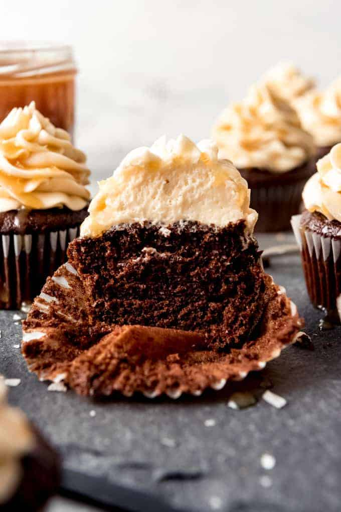 An image of a chocolate cupcake with salted caramel frosting that has been sliced in half.