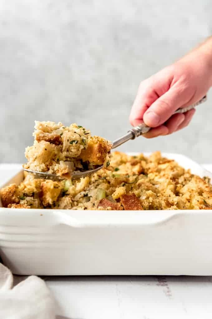 An image of a hand lifting a scoop of cornbread dressing out of a white baking dish.