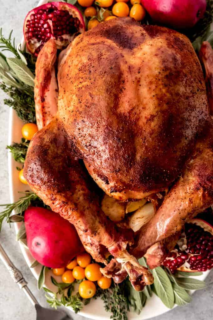 An image of a nicely browned whole Thanksgiving turkey on a serving platter surrounded by fruit and herbs.