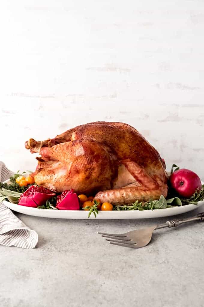An image of a whole bacon roasted turkey on a serving plate.