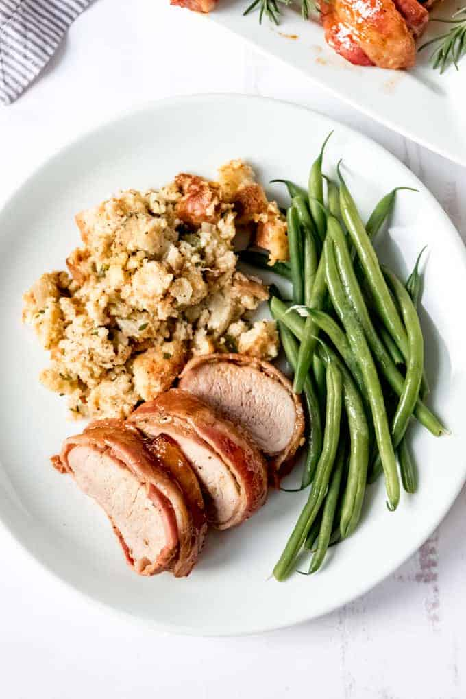 Another image of a bacon-wrapped pork tenderloin on a white plate with cornbread stuffing and green beans.