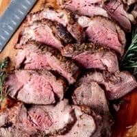 An image of a sliced garlic herb butter beef tenderloin roast on a cutting board.
