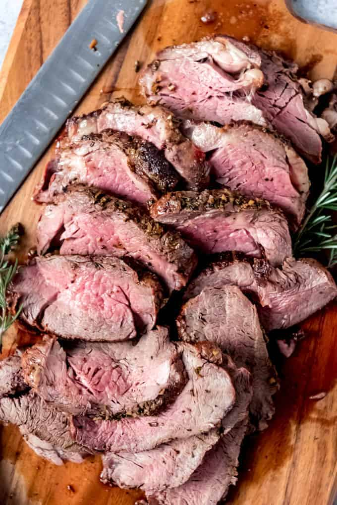 An image of a sliced garlic herb butter beef tenderloin roast on a cutting board.