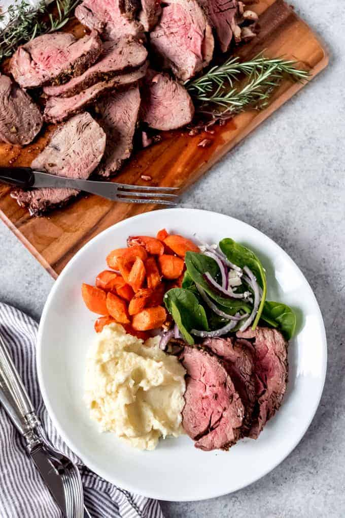 An image of a plate of sliced beef tenderloin with creamy mashed potatoes, roasted carrots, and salad.