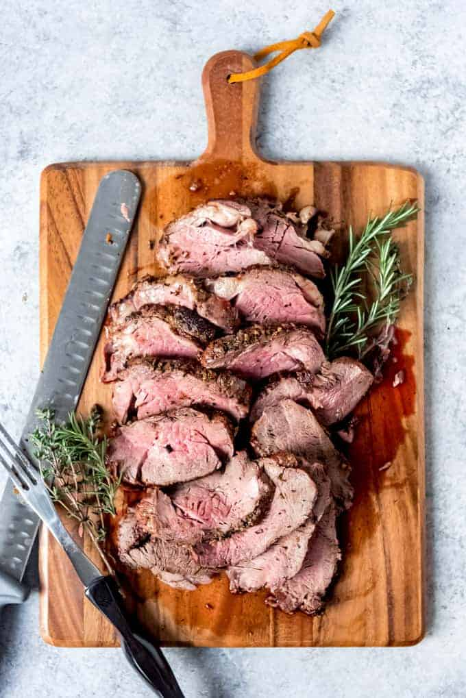An image of a cutting board with a sliced beef tenderloin roast on it.