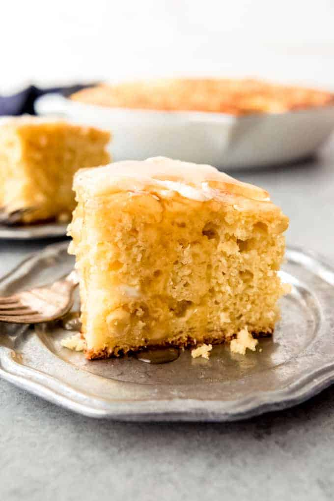 An image of a slice of cottage cheese cornbread topped with butter and drizzled with honey.