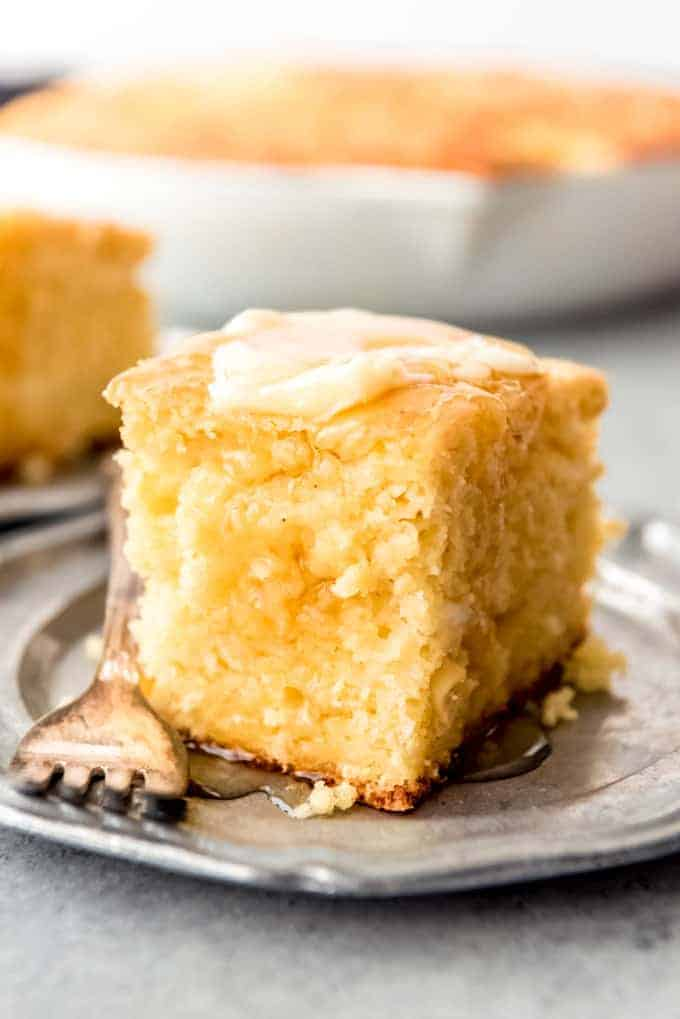 An image of a piece of moist sweet cornbread topped with honey and butter.