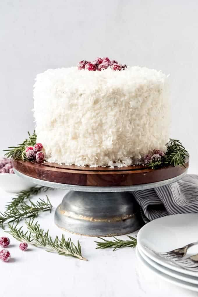 An image of a cranberry coconut cake garnished with sugared cranberries and rosemary.