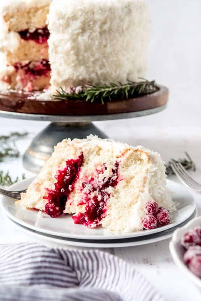 An image of a slice of moist coconut cake layers filled with a homemade cranberry sauce filling.