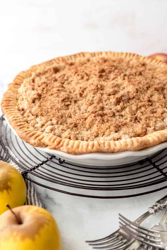 An image of an apple pie with a crumble topping cooling on a wire rack.
