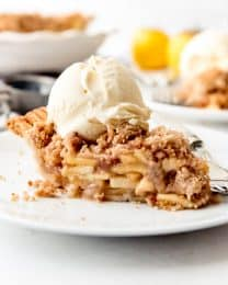 Dutch apple pie on a white plate with ice cream on top and more pie and ice cream in the background