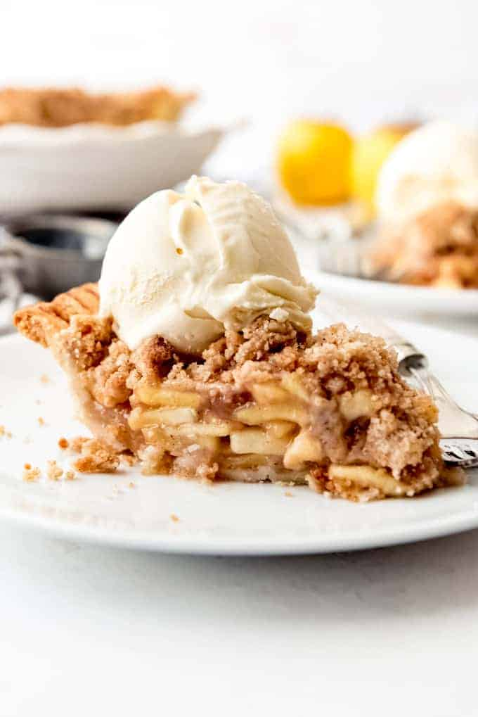 An image of a slice of dutch apple pie with a scoop of vanilla ice cream.
