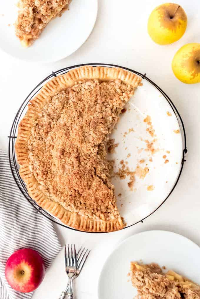 An image of an apple crumble pie with some slices removed and served on white plates.