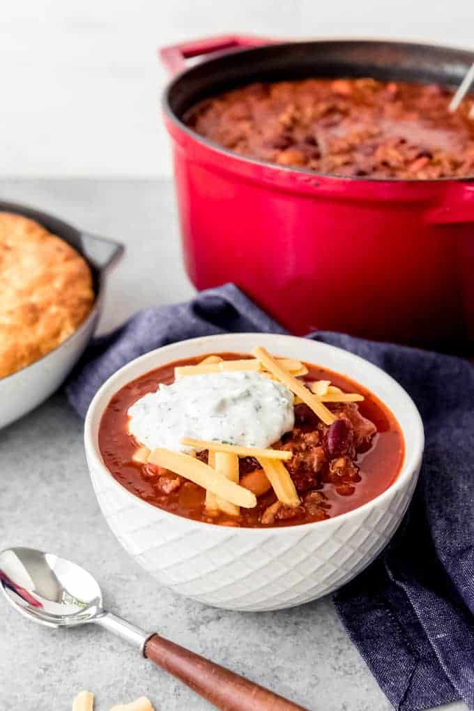 An image of a bowl of classic chili topped with cheese and sour cream.