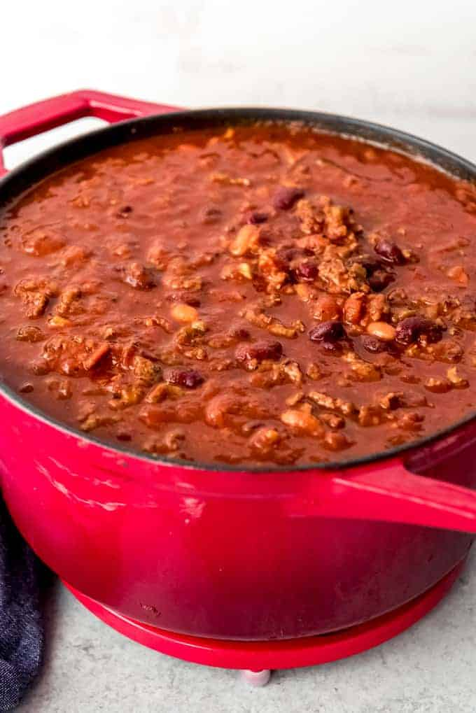 An image of a large red pot of chili with beans and meat.