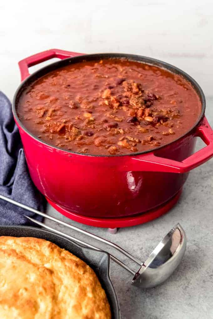 An image of a large red pot of chili next to a skillet of cornbread.