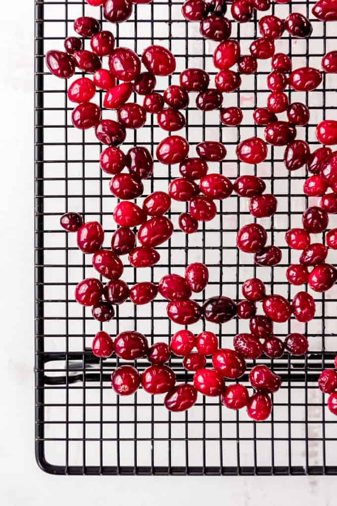 An image of fresh cranberries that have been soaked in simple syrup drying on a wire rack.