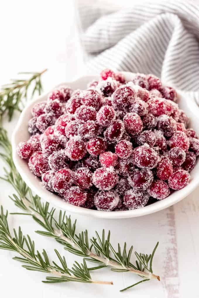 An image of a bowl of sugared cranberries next to rosemary sprigs.