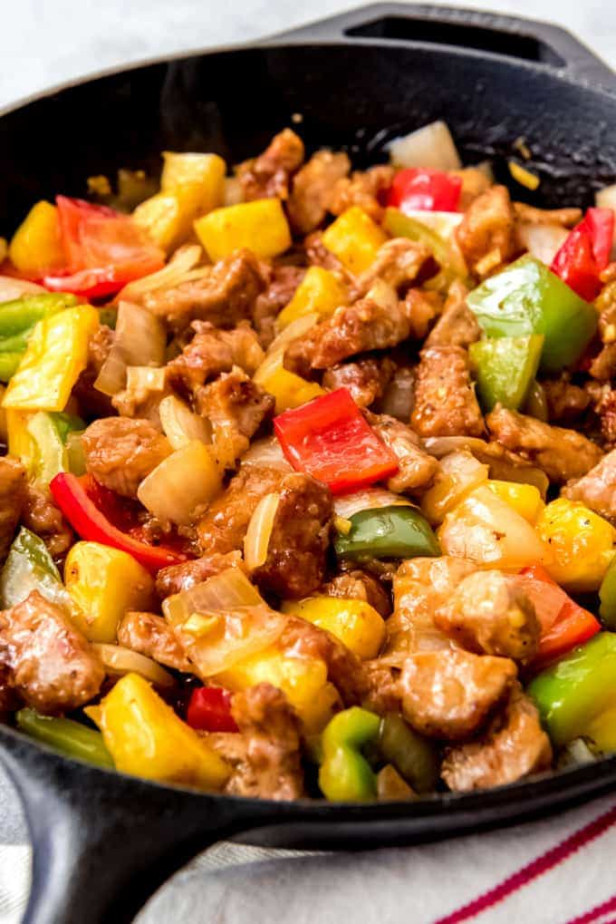 An image of a cast iron skillet full of homemade sweet and sour pork.
