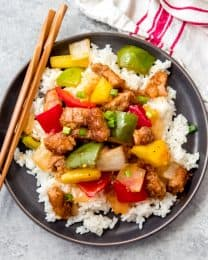 a gray plate topped with a pile of rice and covered in sweet and sour pork with wooden chopsticks to the side
