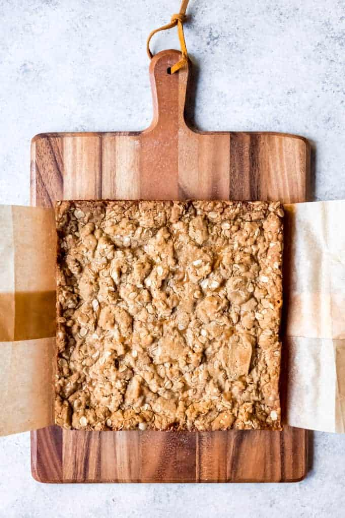 An image of carmelita bars in a parchment paper sling on a cutting board before being cut into squares.