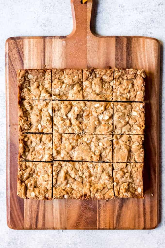 An image of carmelita bars that have been cut into squares on a wooden cutting board.