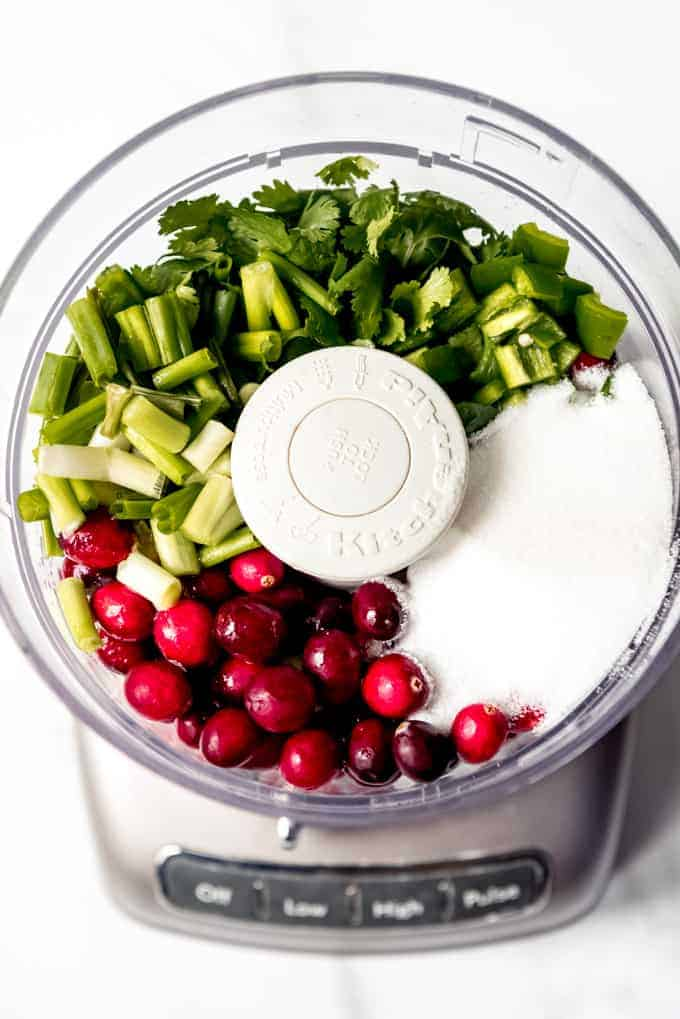 An image of a food processor with cranberries, green onions, cilantro, jalapenos, and sugar.