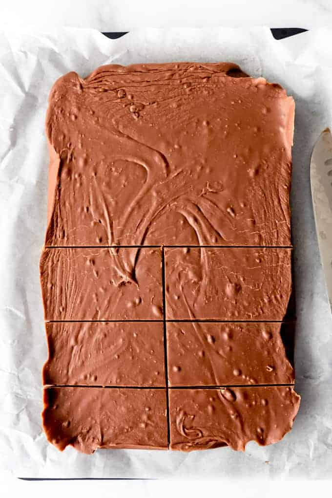 An image of a slab of chocolate fudge made with evaporated milk and marshmallows being cut into bricks.