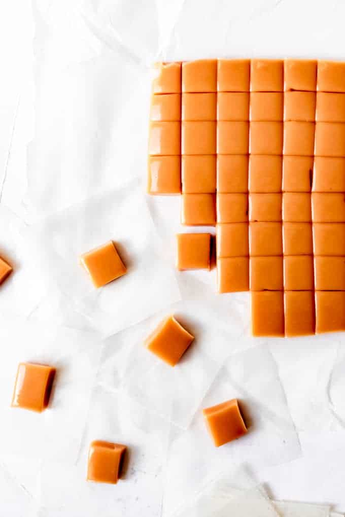 An image of a large piece of homemade caramel being cut into smaller squares.